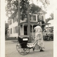 Photograph of a Woman Pulling a Baby Carriage in Parade